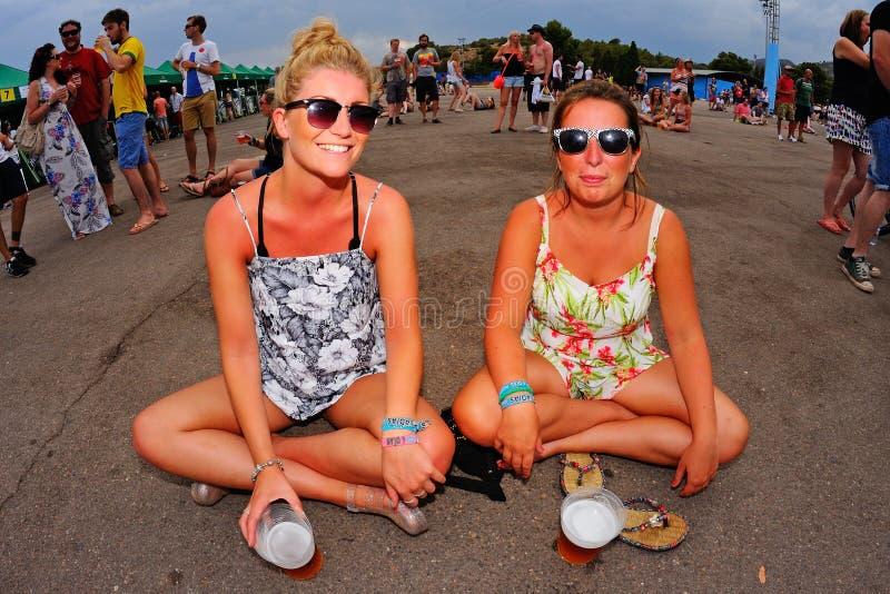 Las mujeres de la audiencia tienen una cerveza en el piso durante un concierto en el festival de la BOLA foto de archivo