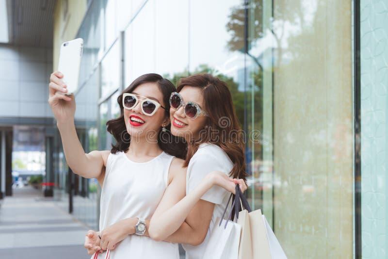 Las mujeres de los mejores amigos que toman el selfie en las caras divertidas que detienen a los compradores que llevan la moda d foto de archivo libre de regalías