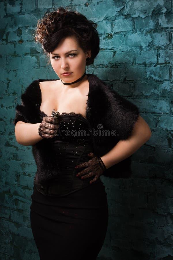 Las mujeres de moda en un negro tiran un arma imagen de archivo libre de regalías