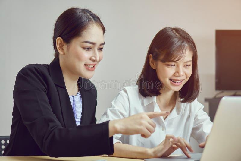 Las mujeres de negocios están utilizando los ordenadores portátiles y los smartphones para trabajar en la oficina fotos de archivo libres de regalías