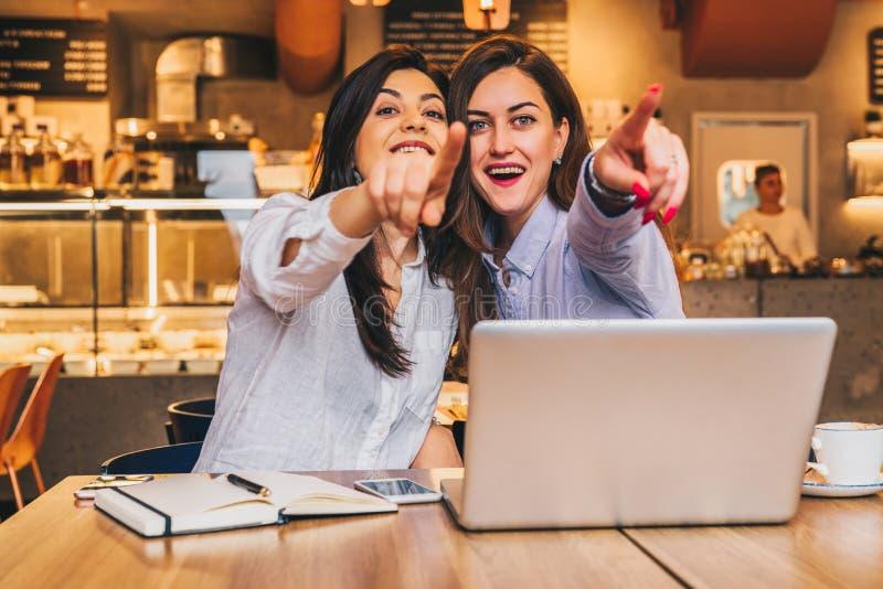 Las mujeres de negocios jovenes se están sentando en un café Las muchachas con sorpresa alegre señalan los fingeres en lo que ven foto de archivo libre de regalías