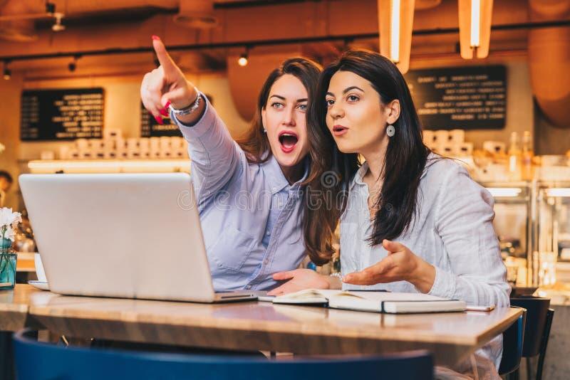 Las mujeres de negocios jovenes se están sentando en un café Las muchachas con sorpresa alegre señalan los fingeres en lo que ven fotografía de archivo libre de regalías