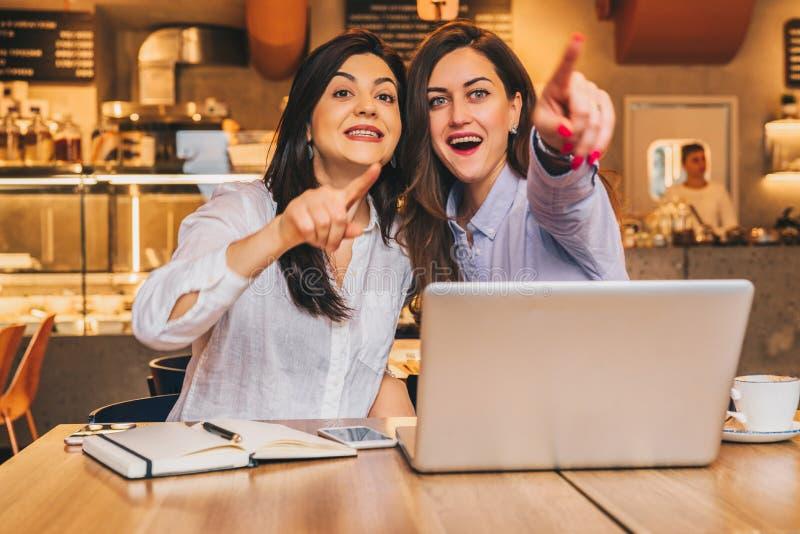 Las mujeres de negocios jovenes se están sentando en un café Las muchachas con sorpresa alegre señalan los fingeres en lo que ven fotografía de archivo