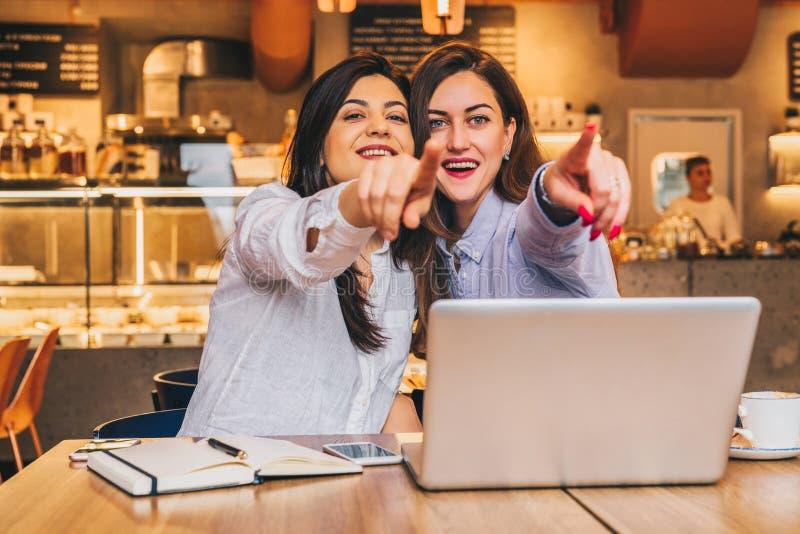 Las mujeres de negocios jovenes se están sentando en un café Las muchachas con sorpresa alegre señalan los fingeres en lo que ven imagen de archivo libre de regalías