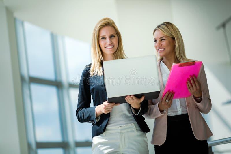 Las mujeres de negocios miran y sonríen conversación con la tableta digital en oficina foto de archivo libre de regalías