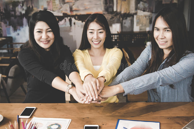 Las mujeres de negocios partner la mano que se une a de la gente después de encontrar acabado gráfico de las finanzas del contrat foto de archivo