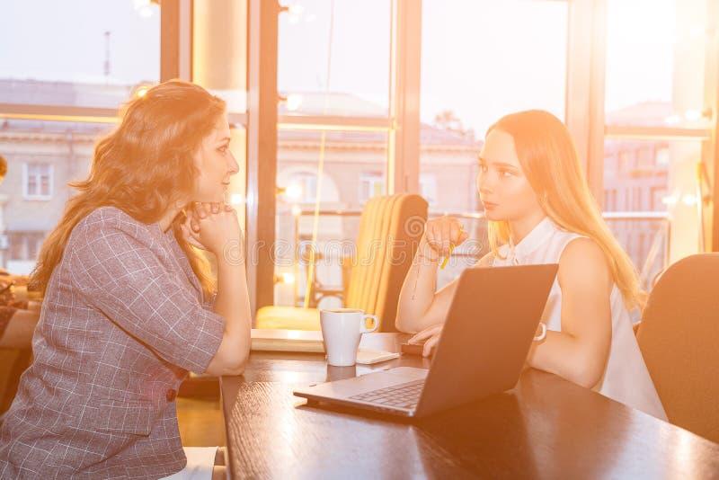Las mujeres de negocios se están sentando en el café en la tabla con el ordenador portátil y la taza de café, hablando de negocio fotos de archivo libres de regalías