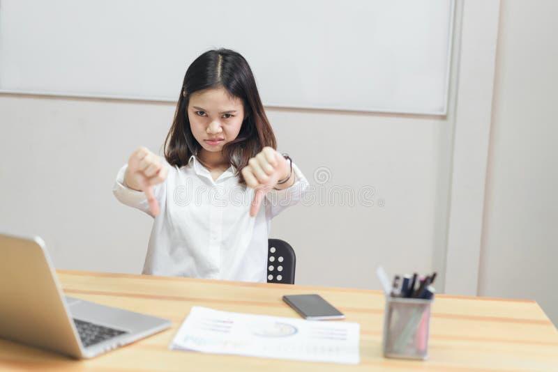 Las mujeres de negocios se sientan en los escritorios de oficina y los pulgares de la demostración de los gestos abajo tienen ave imágenes de archivo libres de regalías