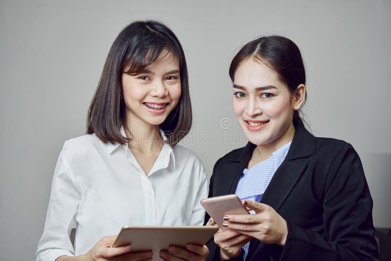 Las mujeres de negocios sonrientes están celebrando la tableta y usar usos en línea imagenes de archivo