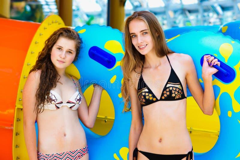 Las mujeres de Smilng en el bikini que coloca el tobogán acuático cercano en la aguamarina parquean imagenes de archivo