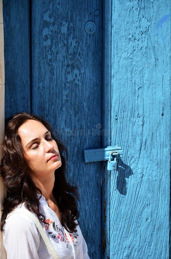 Las mujeres duermen debajo de puerta azul en la calle en la ciudad México de Campeche imagenes de archivo