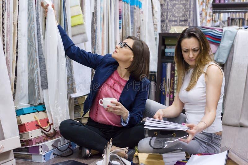 Las mujeres eligen las cortinas de la tela imagen de archivo