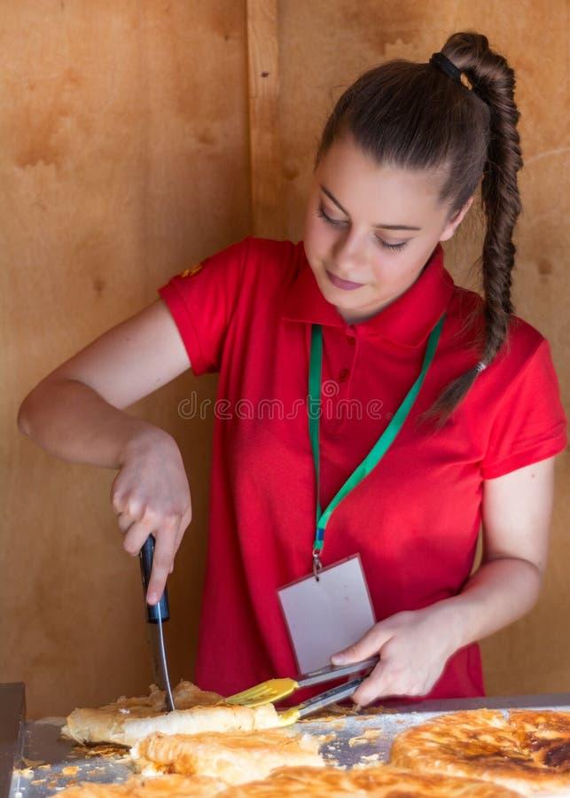 Las mujeres en camiseta roja cortan el burek balcánico con queso con el colector de la comida en panadería foto de archivo