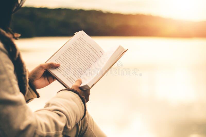 Las mujeres en invierno se sientan leyeron el libro preferido en el día de fiesta imagen de archivo