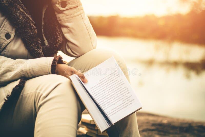 Las mujeres en invierno se sientan leyeron el libro preferido en el día de fiesta fotos de archivo libres de regalías