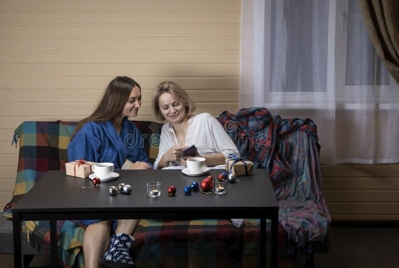 Las mujeres en la ropa casera beben té foto de archivo libre de regalías