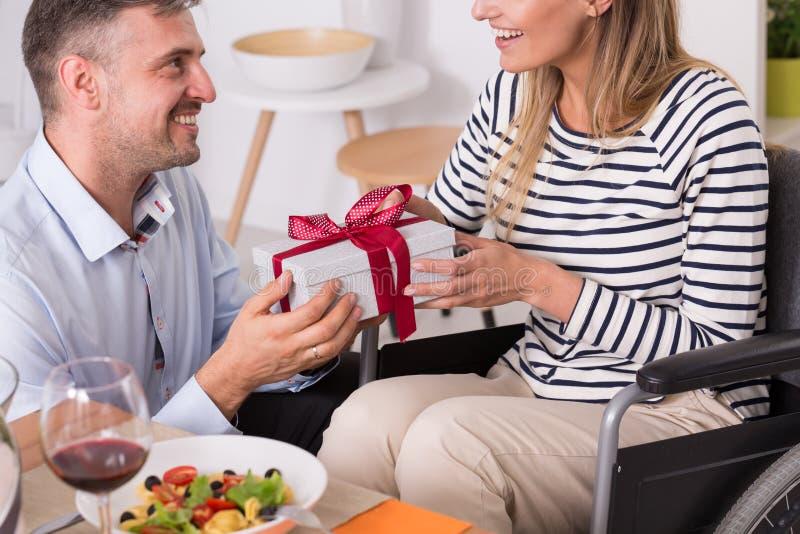 Las mujeres en la silla de ruedas consiguen un regalo foto de archivo libre de regalías