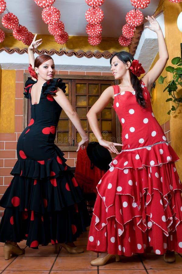 Las mujeres en vestidos tradicionales del flamenco bailan durante Feria de Abril en April Spain fotografía de archivo