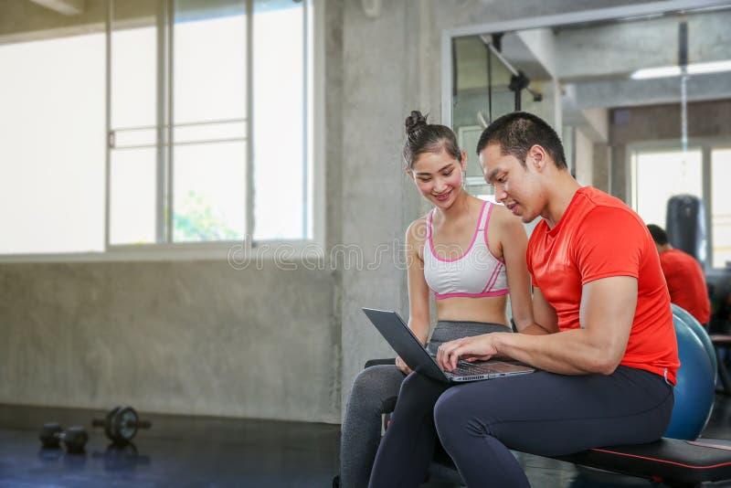 Las mujeres están discutiendo aptitud con los instructores El hablar femenino joven durante entrenamiento en gimnasio Coche femen foto de archivo libre de regalías