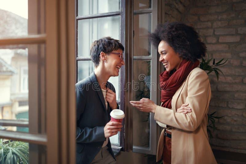 Las mujeres están hablando en tiempo de la rotura en la oficina imagen de archivo libre de regalías