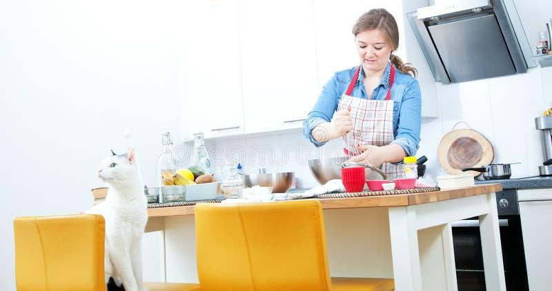 las mujeres están mezclando los ingredientes de una torta en un cuenco inoxidable i fotografía de archivo libre de regalías