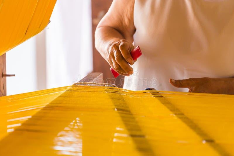 Las mujeres están tejiendo la seda tradicional imagen de archivo