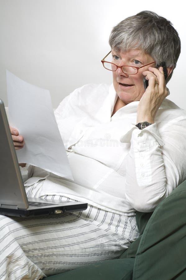 Las mujeres están trabajando en la computadora portátil y la llamada fotografía de archivo libre de regalías