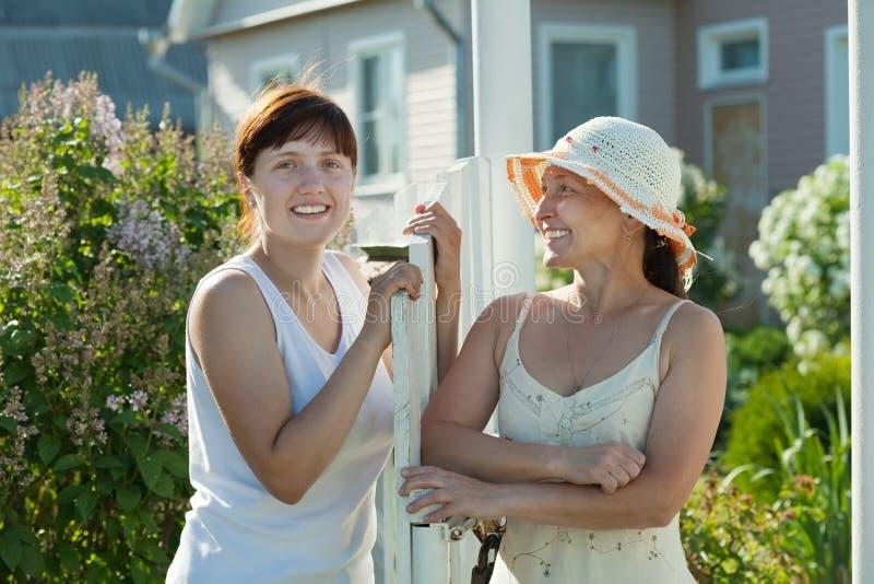 Las mujeres felices acercan al wicket de la cerca foto de archivo