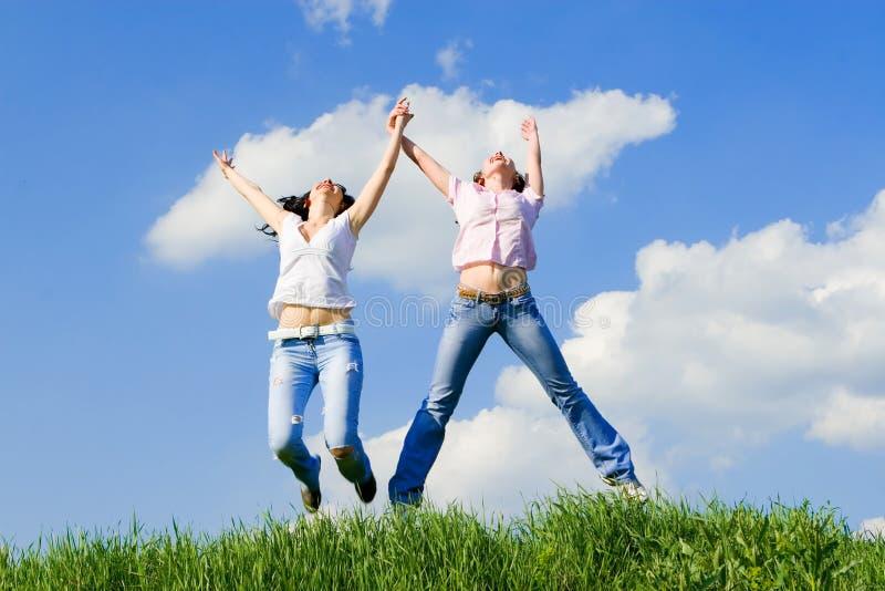 Las mujeres felices están saltando imagenes de archivo