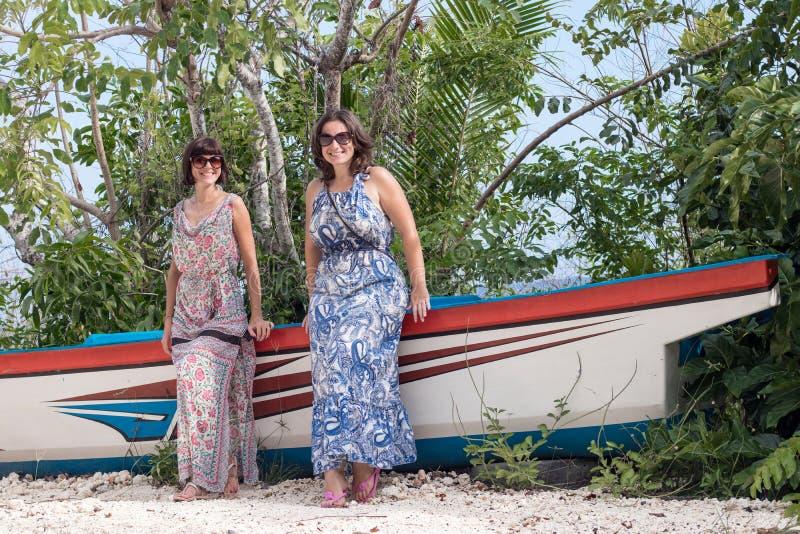 Las mujeres felices jovenes que presentan cerca de la nave vieja en la arena blanca tropical varan Bali, Indonesia foto de archivo libre de regalías