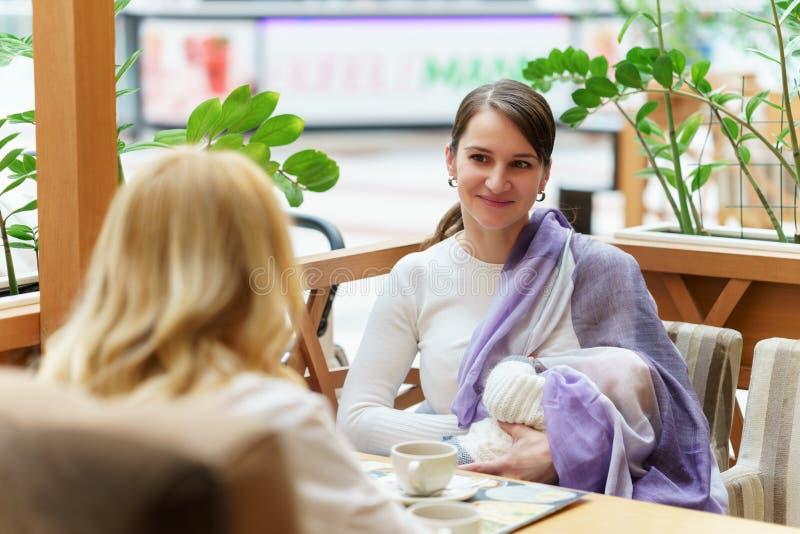 Las mujeres gay europeas jovenes de los pares o de los amigos con el niño se están sentando en banco cerca del carro de bebé blan fotos de archivo libres de regalías