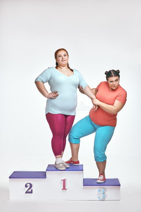 Las mujeres gordas están estando a favor del pedestal de un ganador imagen de archivo libre de regalías