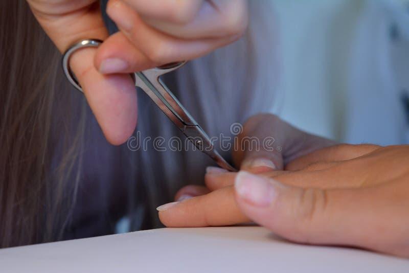 Las mujeres hacen una manicura, laca fotografía de archivo