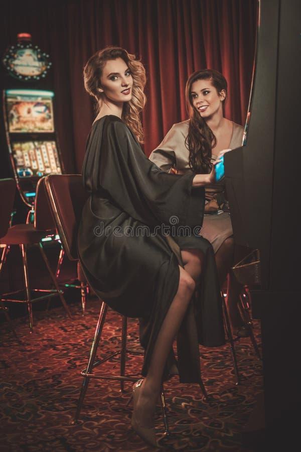 Las mujeres hermosas acercan a las máquinas de ranuras en un interior de lujo del casino imagen de archivo