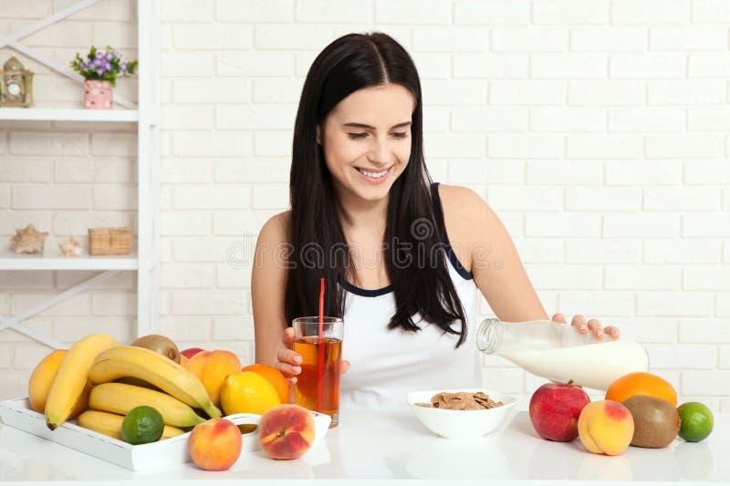 Las mujeres hermosas existen con la piel pura en su cara que se sienta en una tabla y comen a la mujer asiática del desayuno que  foto de archivo libre de regalías