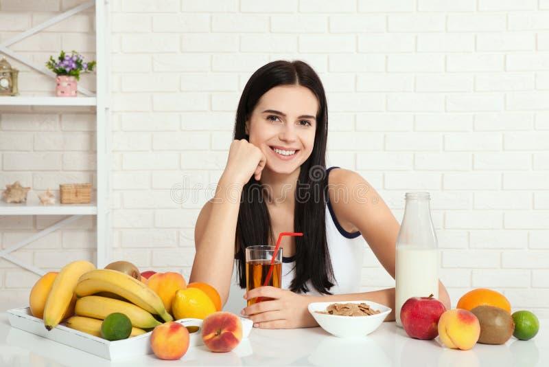Las mujeres hermosas existen con la piel pura en su cara que se sienta en una tabla y comen a la mujer asiática del desayuno que  imagen de archivo