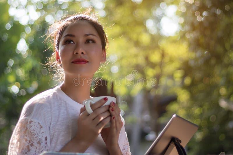Las mujeres hermosas han gozado en el jardín con café y la tabla foto de archivo libre de regalías