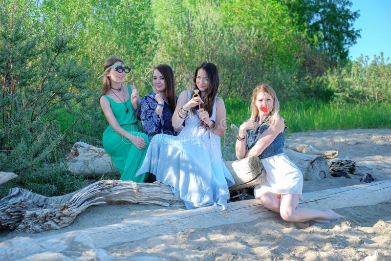 Las mujeres hermosas jovenes en ropa casual y vidrios de sol son que hablan y sonrientes, sentándose en la playa, descansando al  fotografía de archivo libre de regalías