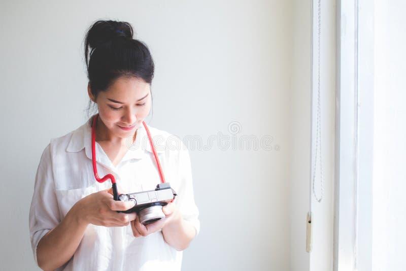 Las mujeres hermosas tailandesas, gente asiática, ataron su pelo y ropa casual que llevaba, llevando una cámara y viendo imágenes imágenes de archivo libres de regalías