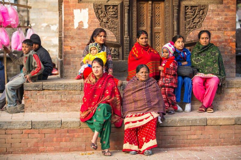 Las mujeres hindúes en sari tradicional se sientan en el viejo cuadrado de Durbar La ciudad más grande de Nepal, su centro cultur imagen de archivo libre de regalías