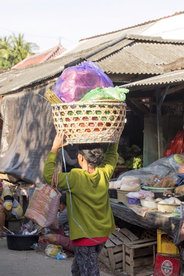 Las mujeres hindúes llevo la carga en la cabeza, - Nusa Penida, Indonesia fotografía de archivo