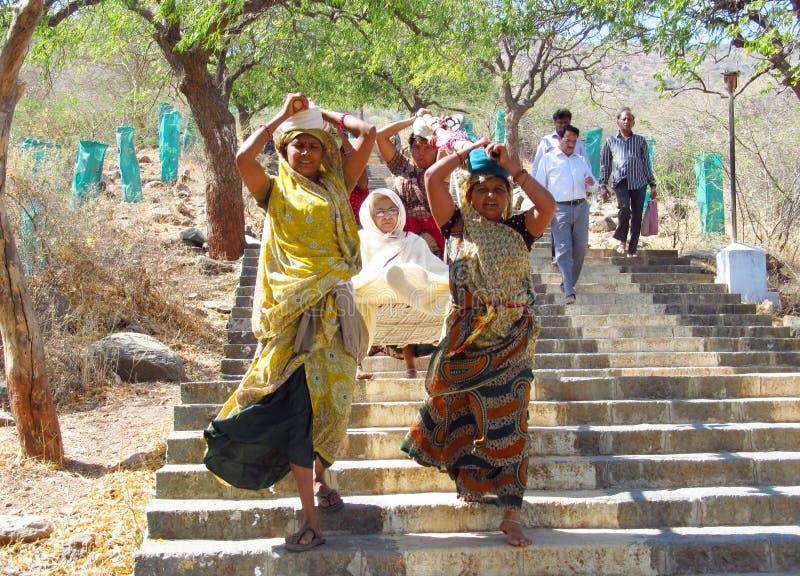 Las mujeres indias en sari llevan el palanquin con la mujer mayor fotos de archivo libres de regalías