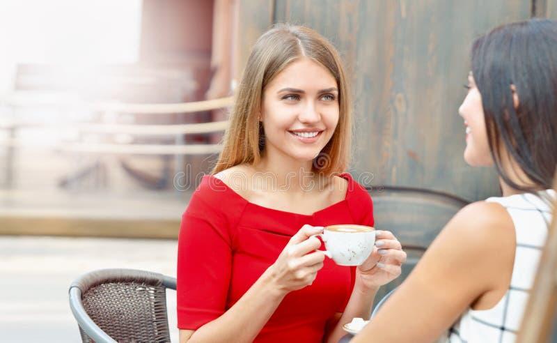 Las mujeres jovenes atractivas beben el café en café al aire libre fotografía de archivo