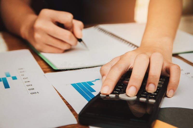 Las mujeres jovenes de la mano están calculando impuesto sobre la renta individual para enviar la información a las agencias de e imagen de archivo libre de regalías