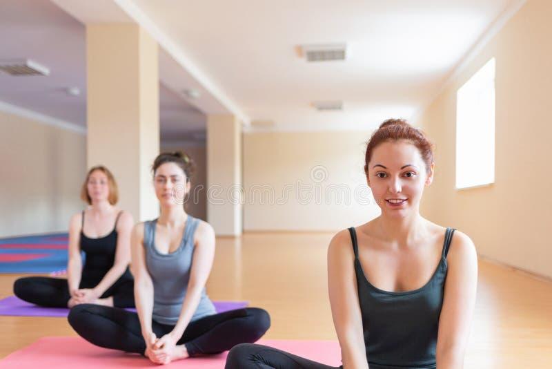 Las mujeres jovenes hacen yoga en la sala de clase El concepto de forma de vida de los deportes, de salud y de equilibrio espirit imagen de archivo