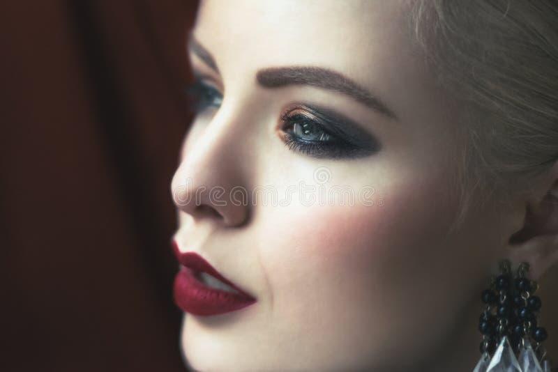 Las mujeres jovenes hermosas con smokey rojo del en de los labios del terciopelo observan fotografía de archivo libre de regalías