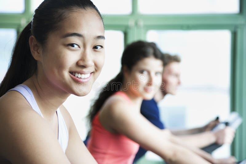 Las mujeres jovenes que ejercitan en aptitud bikes en el gimnasio, mirando la cámara fotografía de archivo libre de regalías
