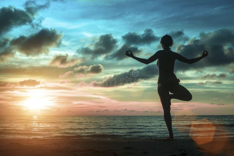 Las mujeres jovenes que se colocan en la yoga presentan en la playa durante una puesta del sol surrealista asombrosa imagen de archivo libre de regalías
