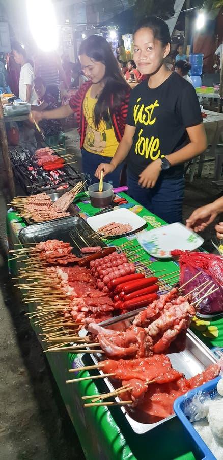 Las mujeres jovenes que venden la comida de la calle asan a la parilla sobre todo productos del pollo y del cerdo cerca de Oslob  imagen de archivo libre de regalías
