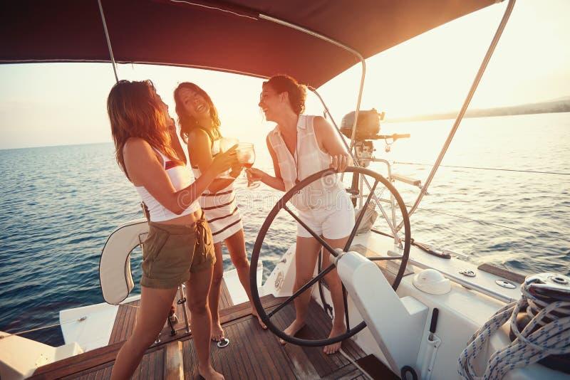 las mujeres jovenes se divierten en el yate en la puesta del sol imagen de archivo